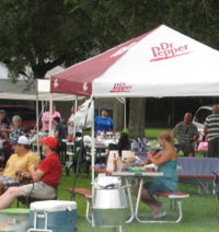 People at an outdoor event with coolers, tents, and shelters.