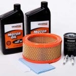 Generator maintenance kit with oil, air filter, oil filter, spark plugs, and funnel.