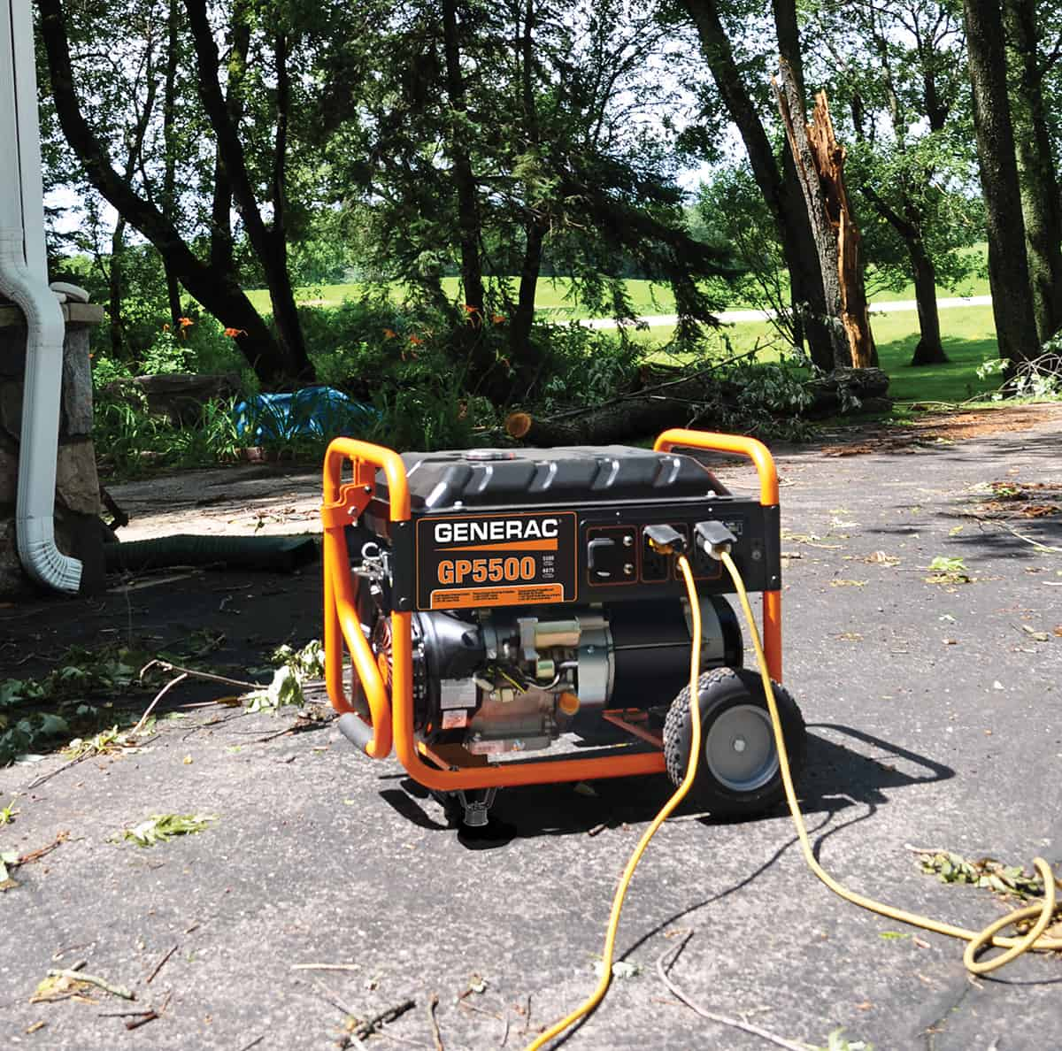 GP5500 Portable Generator on driveway with extension cords with downed trees and limbs.