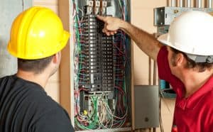 Electricians point at circuit breaker in a service panel