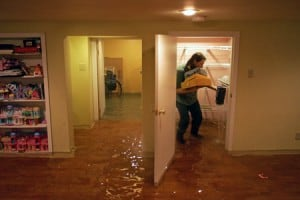A homeowner works to save whatever possible after storm water flooded her finished basement.