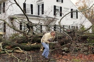 John Constantine makes his way out of his house after winds from Hurricane Sandy toppled a tree fell onto it in Andover, Massachusetts, on October 29, 2012. (AP Photo/Winslow Townson)