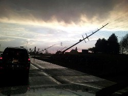 utility poles broken and leaning to one side