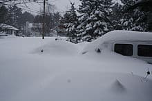 Two vehicles, barely visible and buried in snow after winter storm Nemo.