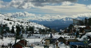 A ski resort in winter showing skiers, lifts, and various buildings at the base of the slope.