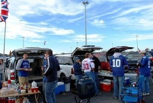 People in team jerseys cooking out and partying at a tailgate party.