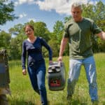 Couple carrying a Briggs & Stratton P2200 Portable Inverter Generator