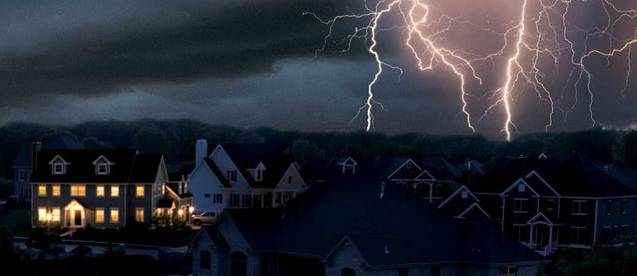 A single home has power in dark neighborhood without electricity after a storm.