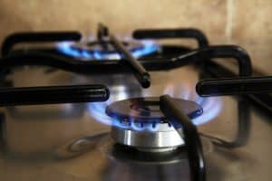 Two lit burners on a gas stovetop.
