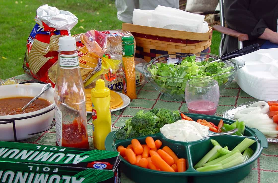 Picnic table with food, condiments, and accoutrements.