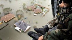 A view of flooded homes from a helicopter with a National Guardsman in the open helicopter doorway.