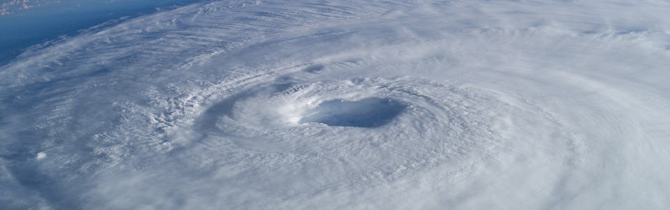 The cyclonic clouds of a hurricane from space.