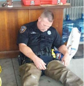 A Texas Sheriff's Deputy sleeps on the floor against a desk after a long night of rescue effots.