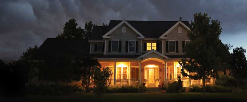A storm approaches a home at night.