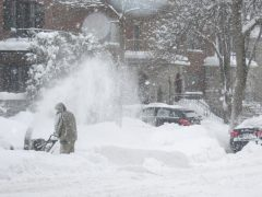 A man uses a snowblower after a blizzard to clear snow from a driveway.