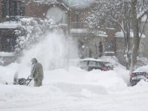 A map operates a snow blower after a heavy snowfall.