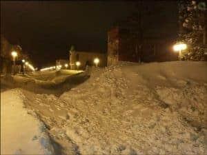 Snow drifts pile up to ten feet high along 1st street in Menominee, MI