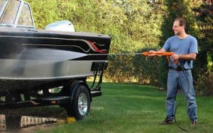 A man washes a boat in his yard with a pressure washer.
