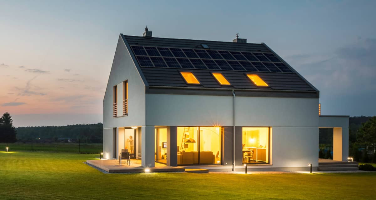 A home at dusk with the lights on has a solar array on the  the roof and battery storage inside.