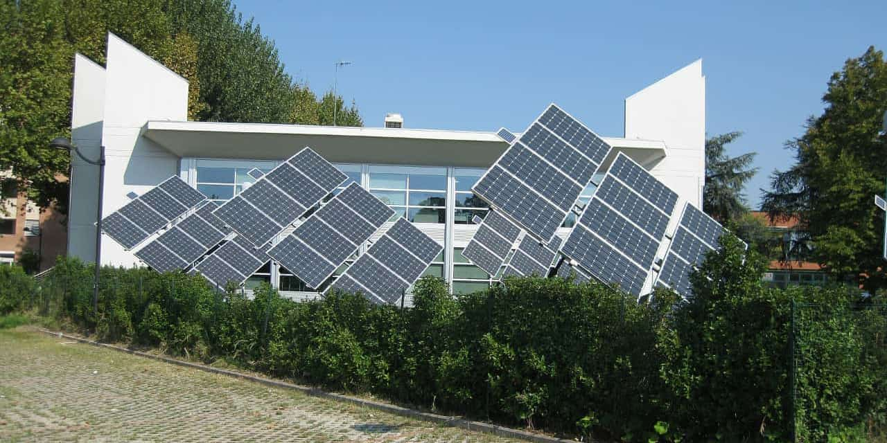 A large solar array produces power for a modern, south-facing home with large windows.