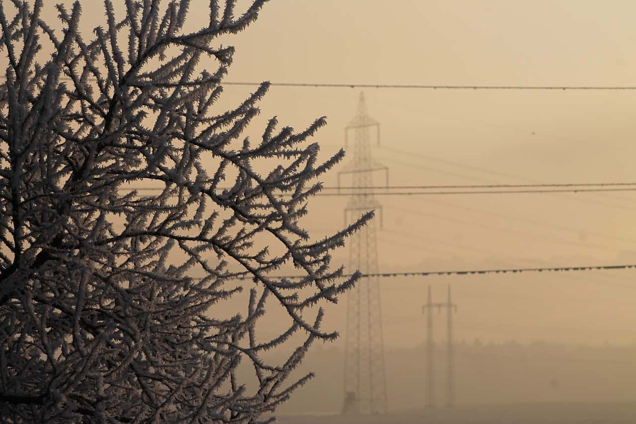Power Lines and Transmission Towers Enveloped in Fog as they Gather Ice During a Winter Storm